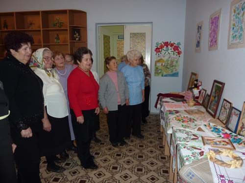"""Жінки із клубу """"Затишок"""" біля експозиції їх робіт, влаштованій до 10-річчя Центру"""